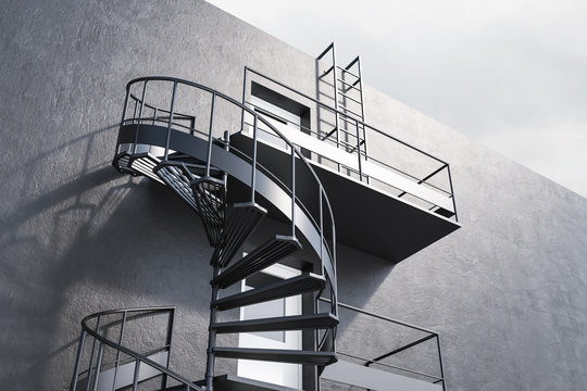 Gray building with spiral fire escape stairs, side