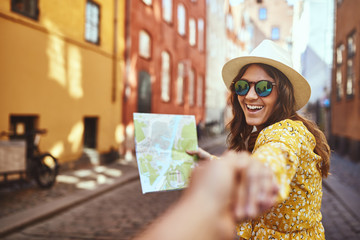 Smiling woman leading someone through city streets by the hand