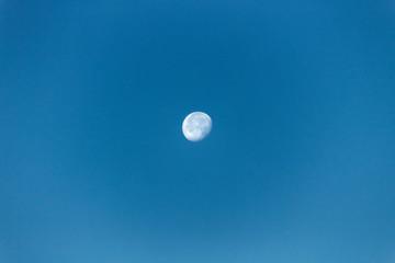 A photograph of near full moon on a clear sky.