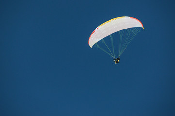 Skydiver under a canopy of a parachute against a blue sky in Georgia, Gudauri