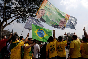 Supporters of Brazil's presidential candidate Jair Bolsonaro holding flags with his picture stand outside Congonhas Airport, in Sao Paulo