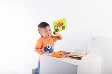 A child on a white background shows how he assembled a designer machine