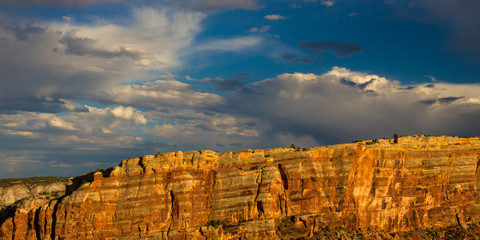 Stunningly beautiful warm sunset light on the steep, sloping stone cliffs of Monument Canyon in Colorado National Monument