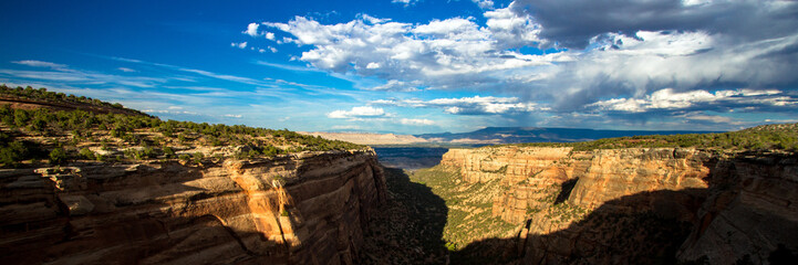 Panorama of sunset light on the steep stone cliffs of Monument Canyon in Colorado National Monument