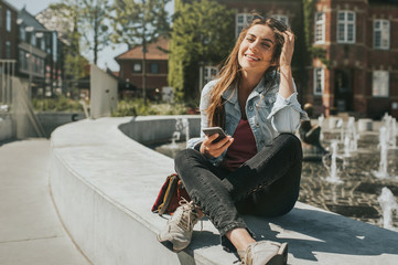 Young beautiful woman sitting in the city center holding a smartphone, smiling.
