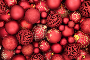 Red bauble christmas decorations forming an abstract background. Traditional christmas greeting card for the holiday season. Top view.