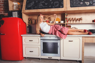 Attractive blonde long hair woman take a rest and laying on the table in the red loft comfortable kitchen