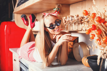 Flirty blonde long hair woman wearing sunglasses laying on the table, smiling and thinking about future vacation in the red loft comfortable kitchen