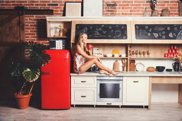 Pretty blonde long hair girl wearing pajama sitting on the comod, drinking her morning coffee and thinking about new day in the red loft comfortable sunny kitchen