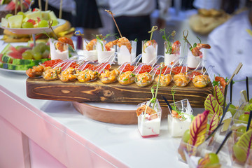 Cocktail Reception at the event, with dry ice Shrimps, burgers, salads, seafood on wooden boards, with sprouted greens