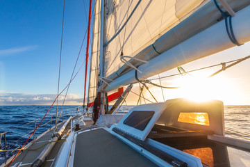 Sailing on sailboat yacht with beautiful sunset light clear blue sky and flat sea in Drake Passage, summer cruising, closeup of boat deck