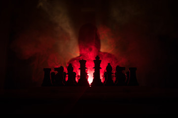 Man playing chess. Scary blurred silhouette of a person at the chessboard with chess figures. Dark toned foggy background.