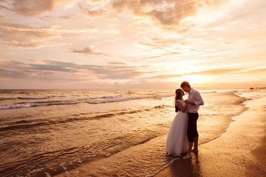 A beautiful couple of newlyweds, the bride and groom walking on the beach. Gorgeous sunset and sky. Wedding dresses, a white luxury dress for a girl. Family concept, honeymoon.