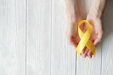 Woman's hand holding yellow ribbon - bladder, liver and bone cancer awareness symbol. Children cancer prevention concept. Isolated background, copy space, close up, top view