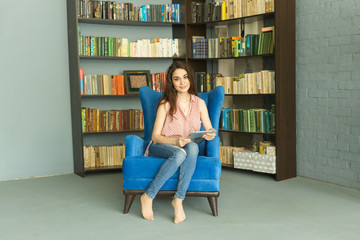 Leisure, people and home concept - Happy relaxed woman in home library