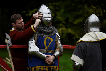 A man prepares a Knight's helmet before dueling with an axe during a medieval combat festival at Claregalway castle in Galway