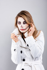 girl in a white coat on a white background with Halloween makeup