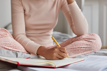 Unrecognizable woman dressed in casual nightwear, writes in notebook, has inspiration for studying. Girl makes notes in diary what happend with her during day before sleeping. Focus on hand with pen