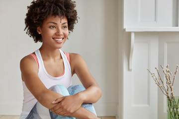 Indoor shot of thoughtful housewife with Afro haircut, has toothy smile, looks into distance, has rest after gymnastic exercises, dressed in sportsclothes, poses against spacious room background.
