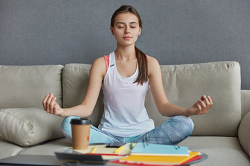 Relaxed concentrated teenager dressed in casual clothes, sits in yoga pose, meditates and has break after hard work, drinks takeaway coffee, poses on comfortable couch at home. Meditation concept