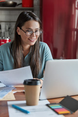 Young woman adminstrative manager reads documentation, has positive expression, looks at laptop computer, drinks takeaway coffee, enjoys cozy atmosphere in kitchen, organizes working process