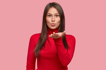 Photo of attractive brunette girlfriend sends sweet kiss by air, bends towards camera with palm opened near chest, folds lips, expresses sympathy, poses over pink studio background. Mwah to you