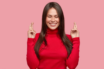 Indoor shot of cheerful brunette girl with satisfied expression, keeps fingers in praying gesture, dressed in red casual clothes, poses against pink background, hopes for good results, makes wish
