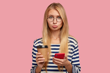 Sad blonde woman with offensive expression, purses lips in displeasure as recieves bad message from friend, drinks takeway coffee, models against pink background. People and lifestyle concept