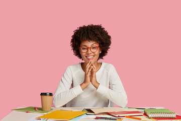 Positive young African American girl concentrated on course work, writes ideas, keeps hands together and smiles positively, happy to solve problems with project, poses against pink background