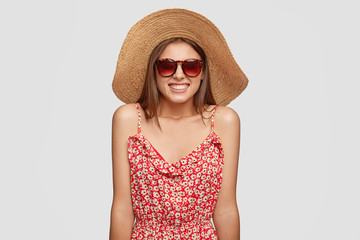 Photo of glad smiling young European woman traveler grins at camera has broad smile, wears summer fashionable outfit, poses against white background. Positive emotions and recreation concept