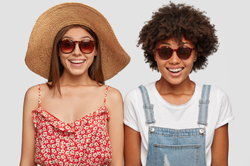 Joyful mixed race women travel together, stad next to each other, smile positively, dressed in fashionable summer hat, dress, overalls, sunglasses, pose against white background. Indoor shot