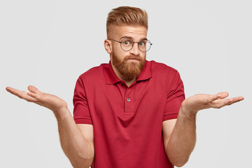 I know nothing. Handsome stylish hipster with thick ginger beard, spreads palms with questionned expression, being unsure, wears transparent glasses, poses against white background. Doubt concept