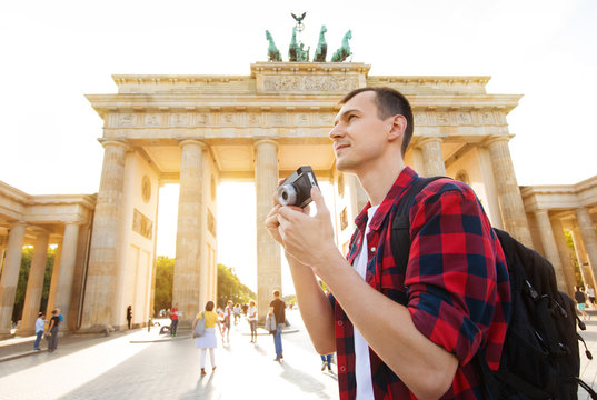 Travel in Berlin, tourist man with camera in front of Brandenburg Gate, Berlin, Germany