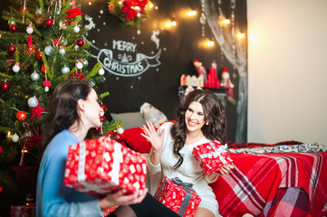 Two women in a decorated room for Christmas laugh, see the gifts, have fun. Girlfriends in the room are preparing for the New Year