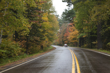 Car driving on a curving road in northern Minnesota with trees in autumn color on a rainy day