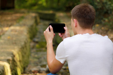 Young man taking pictures using camera his smart phone in nature, park and forest, a small river, a stream. Hand male holding smart phone taking picture of beautiful landscape scenery background.