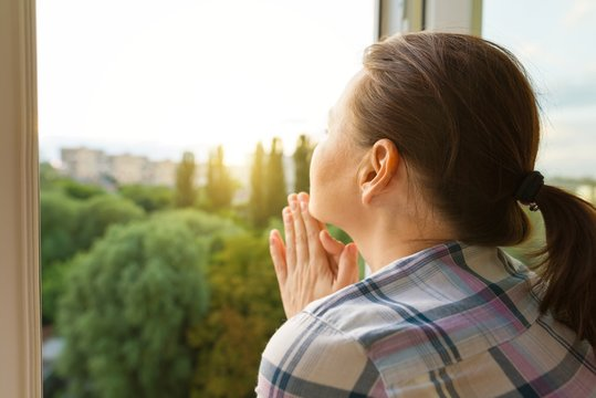 Mature woman looking out the window, close-up view from the back