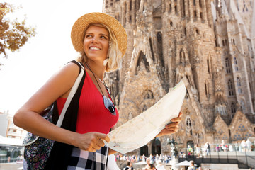 Traveler girl in Barcelona in front of Sagrada Familia. Woman tourist hold and look map, concept adventure