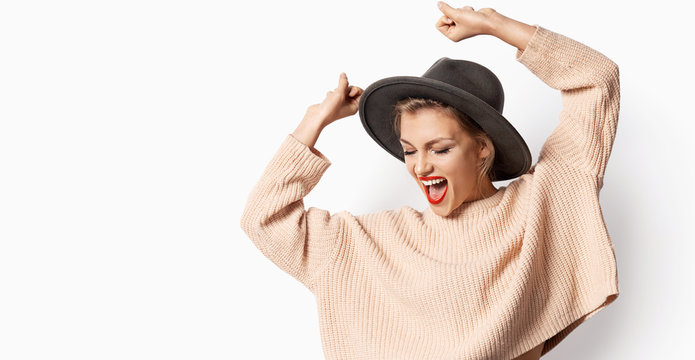 Portrait of beautiful smiling girl in hat and wearing knitted sweater on white background. Woman with bright emotion. Autumn fashion concept.