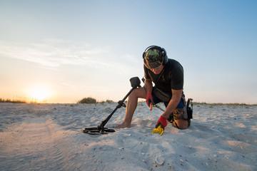 Obraz Man with a metal detector on a sea sandy beach - fototapety do salonu