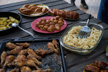 Catering buffet food table with baked potatoes, fried chicken legs, pasta and vegetable salad. People at a party taking different food, outdoor. Colleagues Buffet Party Brunch Dining Concept