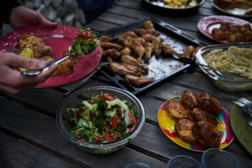 People at a party taking different food, outdoor. Catering buffet food table with baked potatoes, fried chicken legs, pasta and vegetable salad