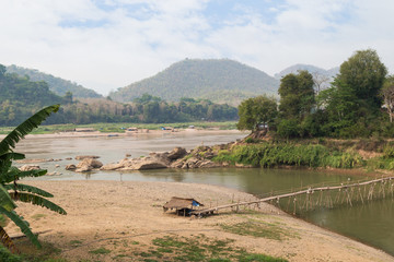 View of Mekong River, a bamboo bridge over Nam Khan River at low tide and lush riverbank in Luang Prabang, Laos, on a sunny day.