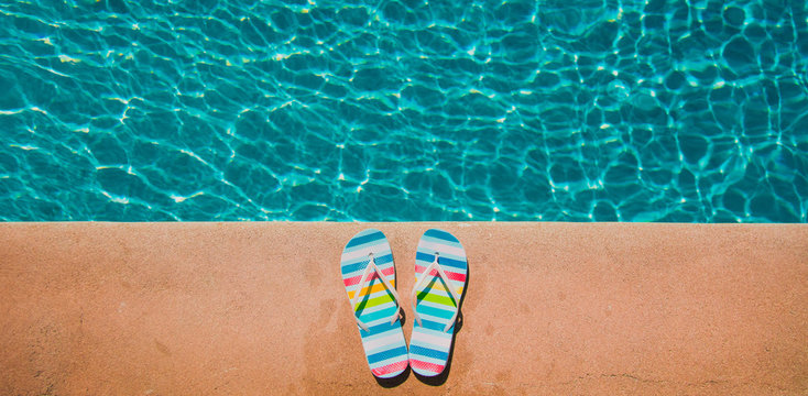 Colored summer sandals near blue pool. Above view