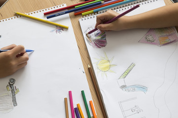 child draws a picture with colorful pens on the white art paper in the lesson.education concept for nursery or school concept.back to school.