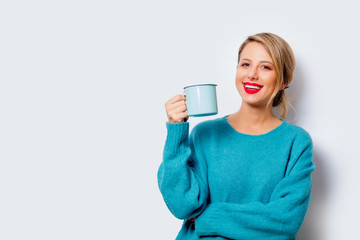 Portrait of a beautiful white smiling woman in blue sweater with cup of coffee on white background, isolated.