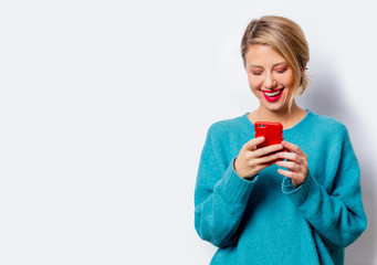 Portrait of a beautiful white smiling woman in blue sweater with mobile phone on white background, isolated.