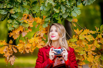 Young woman in red coat and vintage camera in autumn season park.