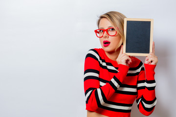 Portrait of a beautiful white woman in red sweater with blackboard on white background, isolated.