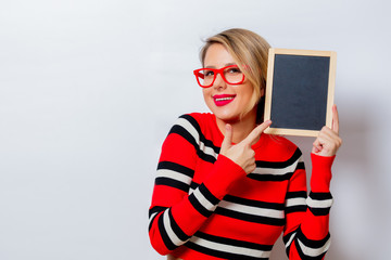 Portrait of a beautiful white smiling woman in red sweater with blackboard on white background, isolated.